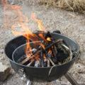 Holzkohlengrill im Garten mit lodernder Flamme